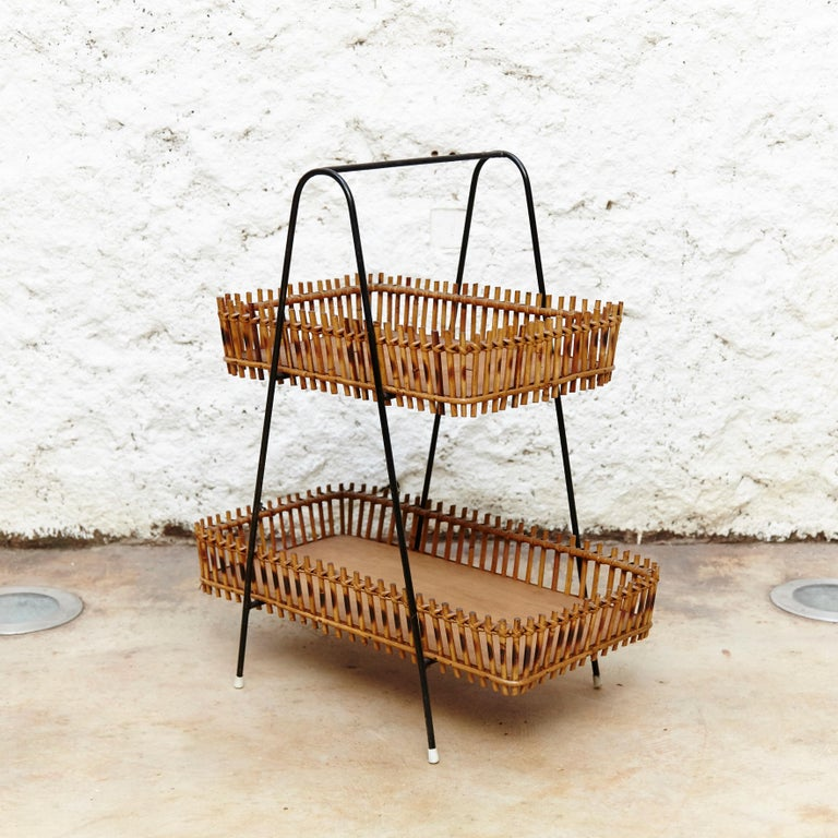 Magazine holders with two levels manufactured in France circa 1950s in rattan and black lacquered metal.  In original condition, with minor wear consistent of age and use, preserving a beautiful patina.