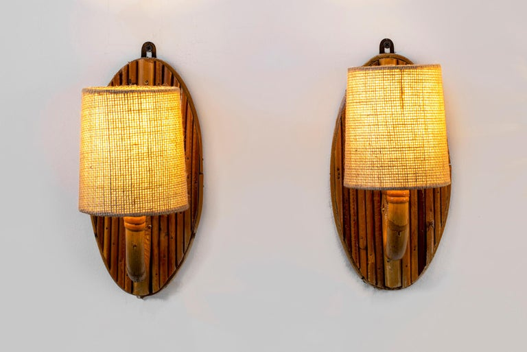 Wonderful pair of French rattan sconces with torchiere arms and textured linen shades. 
