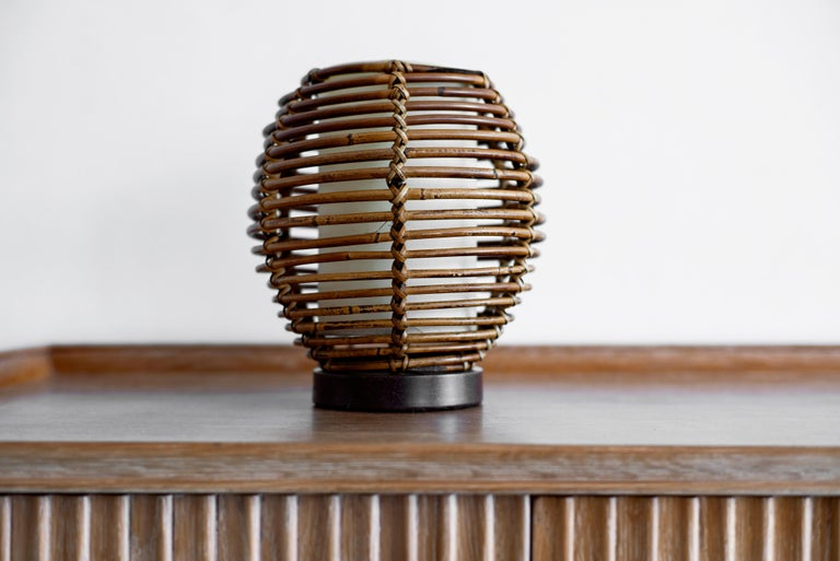 Petite French rattan table lamp with rattan globe shade and inner silk shade diffuser. Circular metal base and newly re-wired. Great vintage condition.