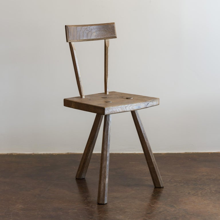 Two three-legged primitive chairs in solid oak featuring hand-sculpted legs and mortise and tenon joints after Jean Touret, France, 1950s.