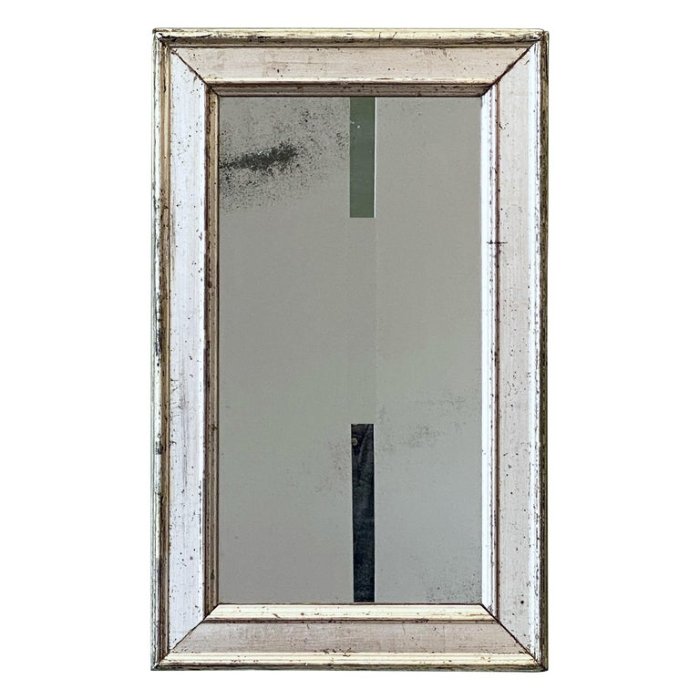 A fine French wall mirror from the 19th c., featuring a silver gilt rectangular frame around an original mirrored glass.  Dimensions are H 19 1/2 inches x W 12 1/4 inches.
