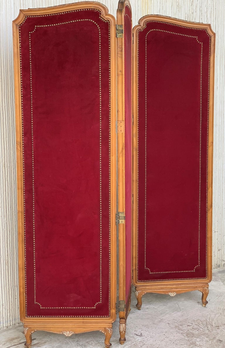 French red velvet three-panel screen adorned with antique brass tacks. Beautiful carved legs and tops.
