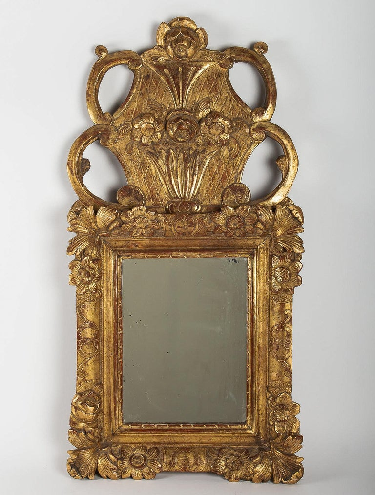 French Regence Provençal period, small giltwood top-front mirror, circa 1715-1723  An elegant and decorative, small carved giltwood top-front mirror, decorated with flowers décoration.  Lovely Provençal Regence period mirror, circa