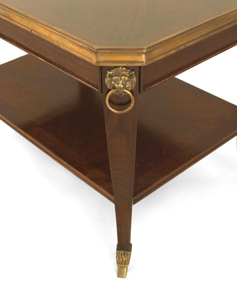 French 1940s (Regency style) mahogany coffee table with a shelf and bronze lion head trim, hoof feet, and an edge supporting an inset glass top (stamped: JANSEN).  Maison Jansen was aParis-basedinterior decorationoffice founded in 1880