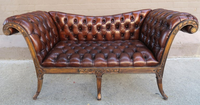 French Regency style carved wood sofa upholstered in tufted beautifully distressed leather and detailed with nailheads. The sofa is finely carved and has parcel gilt detailing.  Measures: Seat height 18