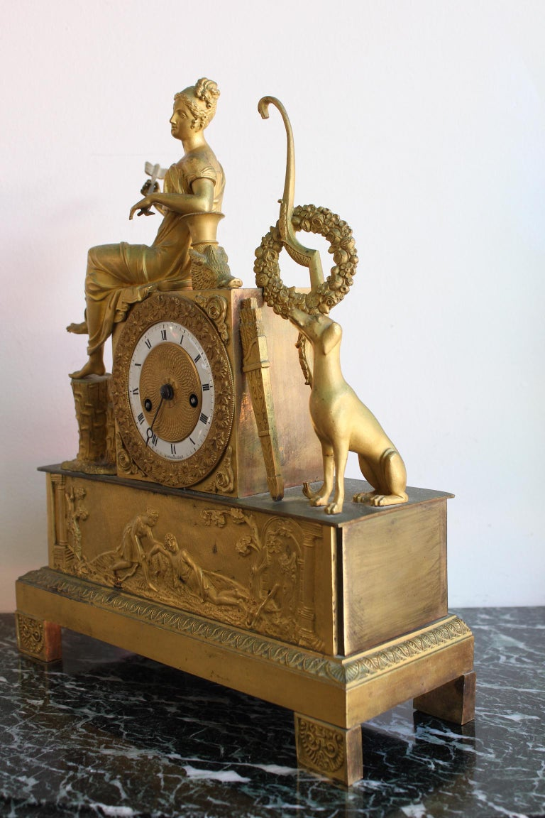 French Restauration clock in gilded bronze, representing an Allegory of hunt. Dimensions: Width 28.5cm, depth 10.5cm, height 35.5cm.