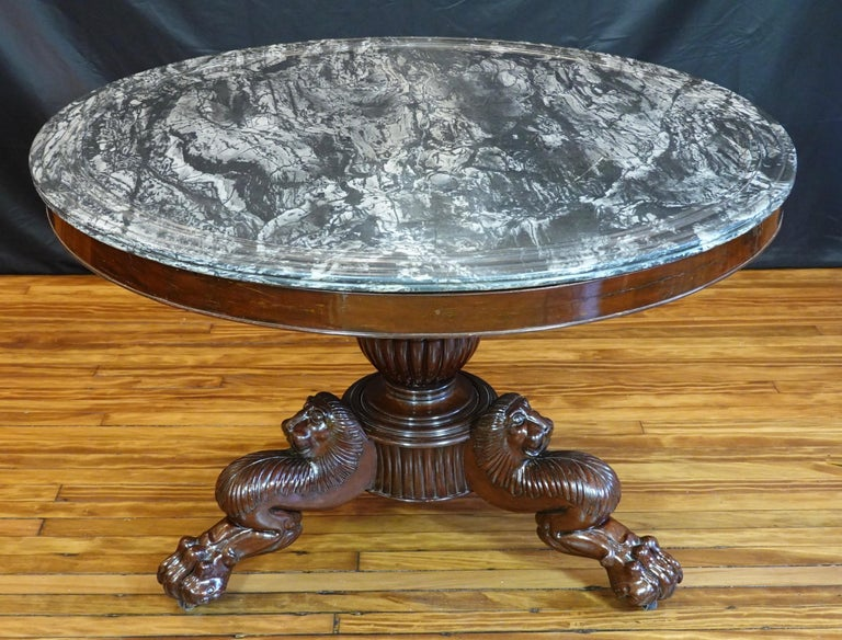 Large French Restoration period (circa 1815-1830) mahogany center table with variegated black and white marble top. The base stands on a central lobed pedestal with three legs with impressive carved lion's heads terminating in paw feet with casters.