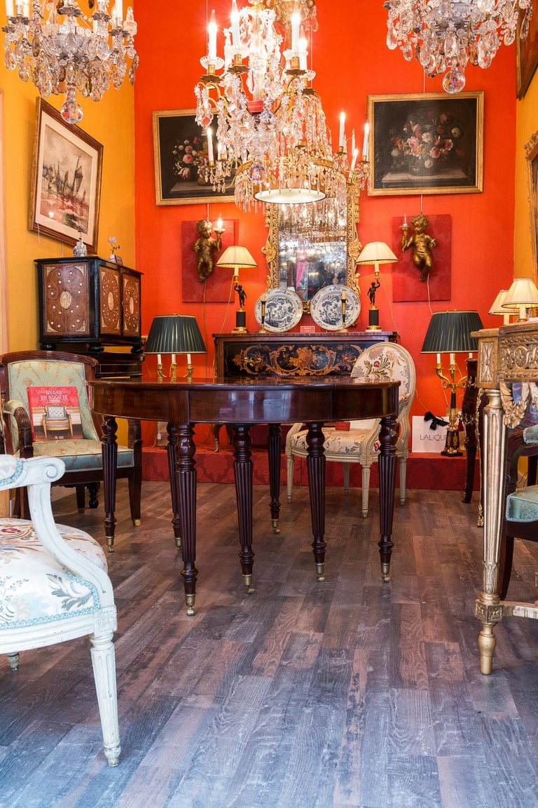 French restauration period mahogany dining table, circa 1815-1820  A beautiful and attractive French early-19th-century Restauration period mahogany large dining table, circa 1815-1820. The table is raised on eight ormolu casters with ormolu