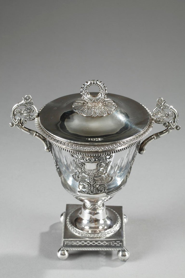 Lightly tapered candy dish in silver and crystal. The rim is ornamented with an openwork geometric frieze, and the paunch features a sculpted silver balustrade vase and two birds standing facing each other on either side of the vase. The birds are