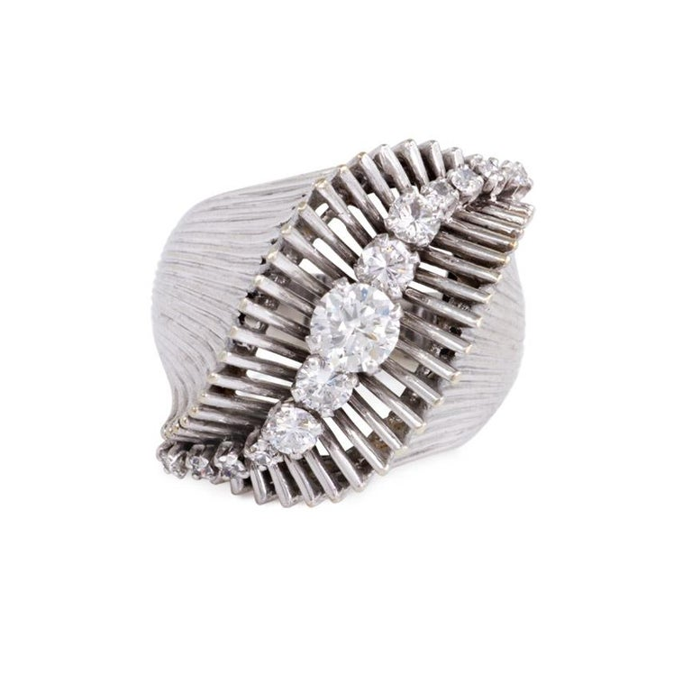 A Retro white gold and diamond ring with flared gold wire top of swirl design, centering on a curved row of graduated diamonds, in 18k and platinum.  France.  Atw 1.00 ct.  Current ring size: 6.5 Top dimensions: approximately 7/8 inches wide, sits