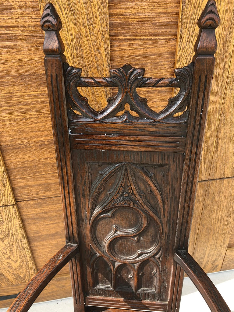 French 1847 Gothic Cathedral armchair. The fantasy element of the gothic tradition is alive and well in this symbolic carved luminary and stately armchair. It is well worn with time and the wood is as smooth as driftwood however grooved and almost
