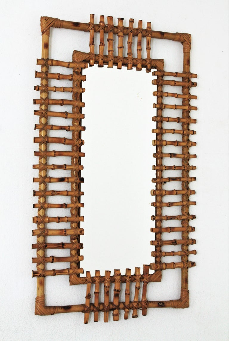 A beautiful handcrafted French Riviera rectangular shaped bamboo mirror, framed by cane rays. France, 1950-1960. This piece has all the taste and freshness of the Mediterranean style. Interesting to be used in a powder room. Place it alone or