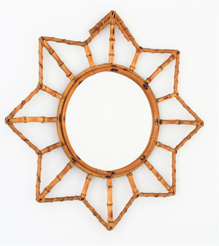 A lovely Mid-Century Modern handcrafted bamboo and rattan mirror with star shape and all the taste of the Mediterranean French Riviera taste.  France 1950-1960. Glass diameter: 25.5cm.