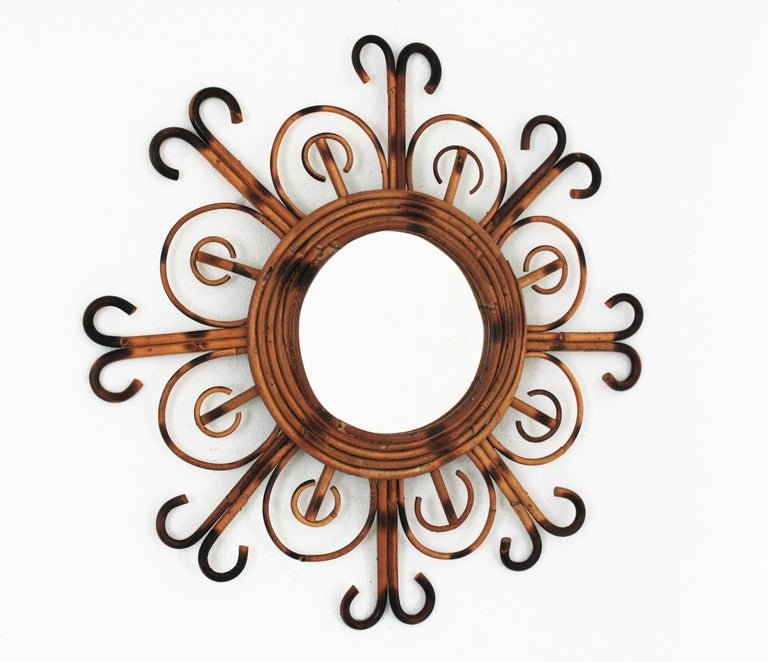 Eye-catching flower shaped / sunburst rattan mirror with pyrography details. Manufactured in France at the 1950s.  This wall mirror features a rattan frame made of rattan petals alternating wiht curved ended rays. This piece has all the taste of