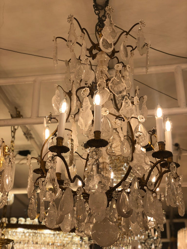 An eight armed late 19th century birdcage chandelier with central baluster stem surrounded with Rock crystal mounted on top with a plume and teardrops below which are featured four rosettes. The stepped shoulder frame features a further rosettes.