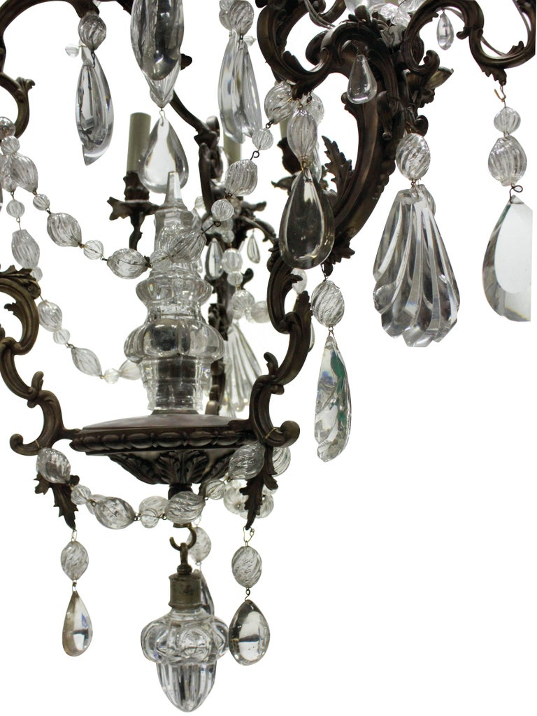 A French Rococo bronze chandelier hung throughout with interesting cut and blown glass drops and swags with a central spire.