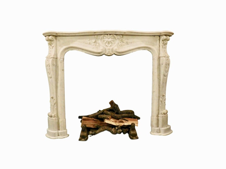 An important French Louis XV Carrara marble fireplace mantel. Serpentine top surface shelf, supported with intricately carved jambs ending in an acanthus leaf headed scrolled foot, the upper portion of jamb with floral and foliage decoration