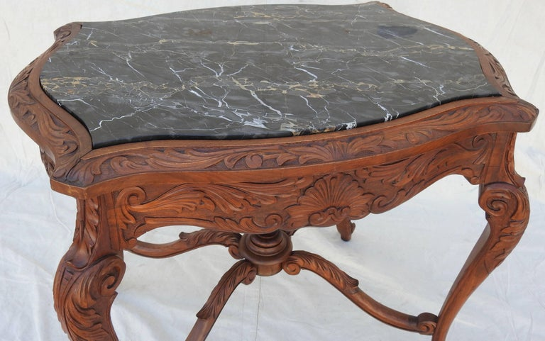 Offering this beautiful French Rococo marble-top walnut parlor table. Stunning hand carved detail of scrollwork, foliate and floral designs grace the skirt of this table. It is topped with black marble with veins of silver gray and brown. The marble