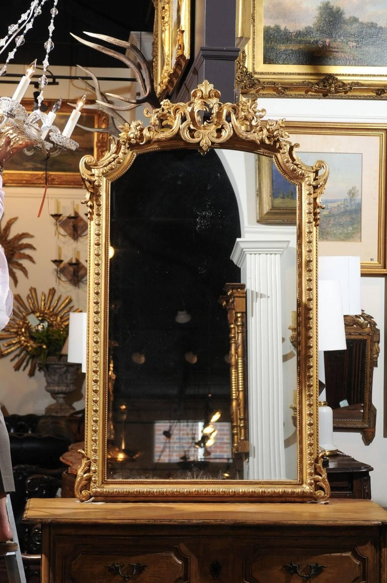 A French Rococo style giltwood mirror with carved crest from the 19th century. This vertical French Rococo style mirror features a trapezoidal frame, adorned with delicate beads, and egg motifs set inside a guilloche style frieze. Two acanthus
