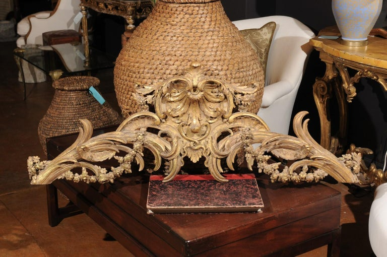 A French Rococo style parcel-gilt and carved wooden architectural swag from the 19th century, with acanthus leaves, C-scrolls and swag. Born in France during the 19th century, this architectural element features an exquisite hand-carved crest,