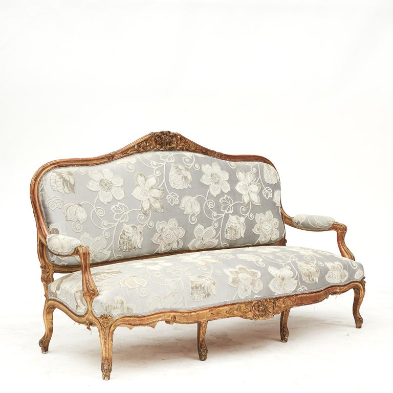 French Rococo style sofa bench decorated with carved foliage motifs.