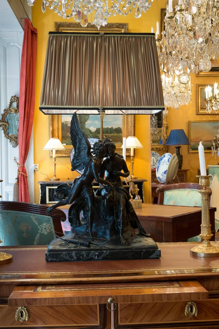 A beautiful finely chiseled and patinated bronze group, depicting an annunciation symbolized by an angel having put down his quiver and its bow to the feet of a nymph seated on a hillock, raised on a base of sea-green marble.  Our sculpture