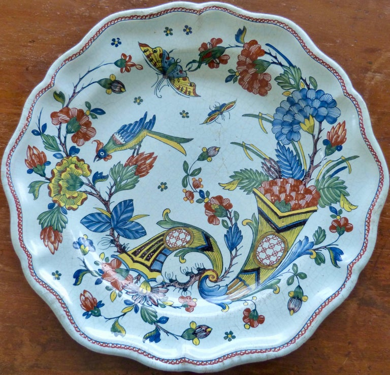 A French Rouen large Faïence charger with scallop-shaped edges. Picturing the sign of prosperity double Cornucopia and with blooming flowers, butterflies and a bird. Decorated in a typical polychrome palette of colors composed of green, blue, iron