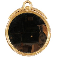 French Round Giltwood Mirror from the 19th Century with Swag Themed Crest