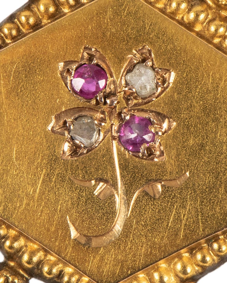 From the era of Napoleon III, of 18k two-color gold set with a tiny ruby and diamond flower, with openwork border  Paris, 19th century, with French hallmark  1 in. (2.5 cm)