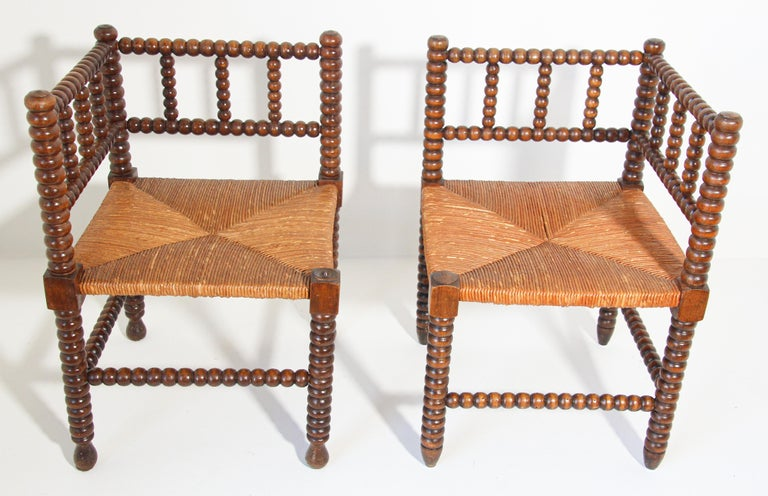 Pair of French rush-seat corner chairs, Coin du Feu. Pair of French Provincial-style carved fruitwood armchairs with open backs and rush seats.  Pair of antique sturdy useable chair, wood stick and ball craftsmanship corner chair with original rush