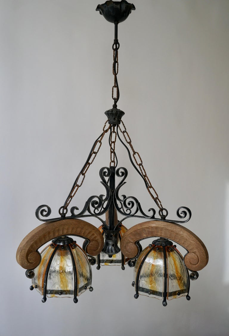 A vintage French three-light rustic wrought iron and wood three arms chandelier with beautiful glass shades.