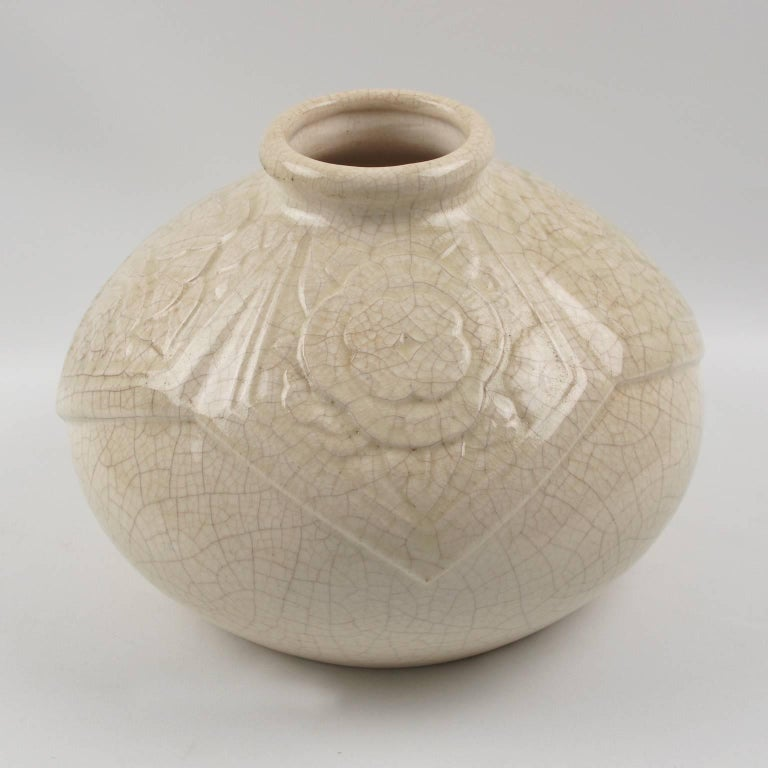 Elegant Art Deco vase by Saint-Clement, France. Large ceramic vase with off-white crackle glaze finish. Features a large puffy round shape with small collar opening and detailed carved stylized floral design all around collar with geometric shape.