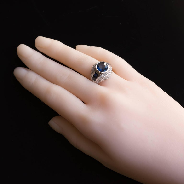 Ring in Platinium and 18 carat yellow gold, dog and eagle heads hallmarks.   This splendid sapphire and diamond dome style ring features a good sized bezel set round sapphire of a deep blue. This is accentuated by 2 square sapphires at each side,