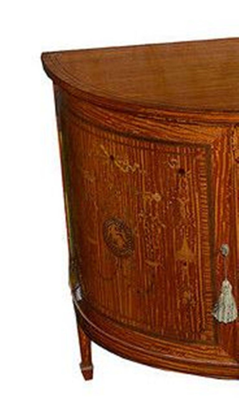 A French satinwood and marquetry inlaid D shaped sideboard of exceptionally fine quality.  The side and door panels and mahogany lined fronts, all with classical influenced inlays incorporating seated Grecian figures and urns and trailing