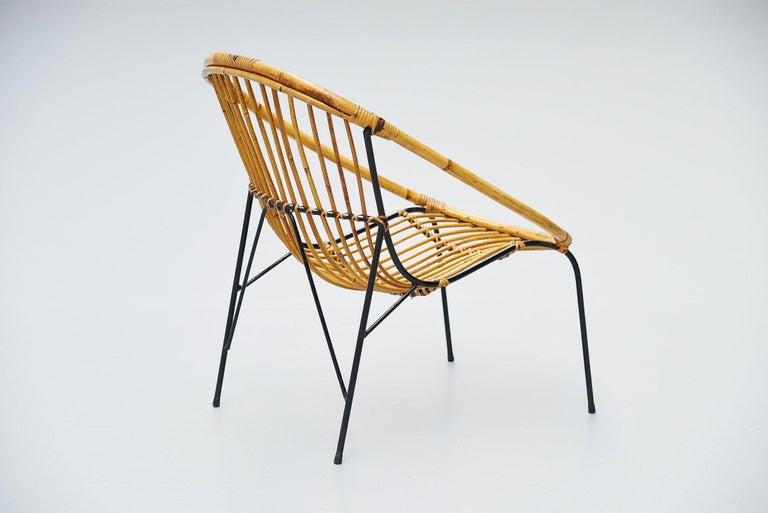 Very nice sculptural rattan small lounge chair made by unknown designer or manufacturer in France, 1950. The chair has a solid steel frame, black painted and rattan handwoven seat. Very nicely shaped chair, can be finished with a sheep skin for