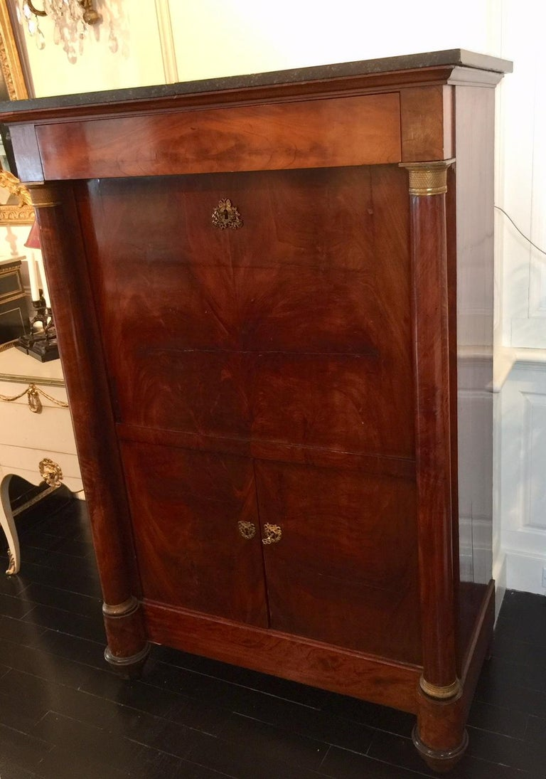 French first Empire period Secretaire à Abattant, also known as a drop-front secretary, fall front or cantilevered desk. Under the dark grey marble top is a secret, entablature drawer. A cantilevered fall front opens to reveal several drawers, a