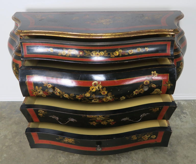 French chinoiserie painted and black lacquered Bombay chest of drawers. The piece is painted in black lacquer with red and gold accent details throughout. There are three large drawers and two smaller drawers on the top for ample storage. The chest