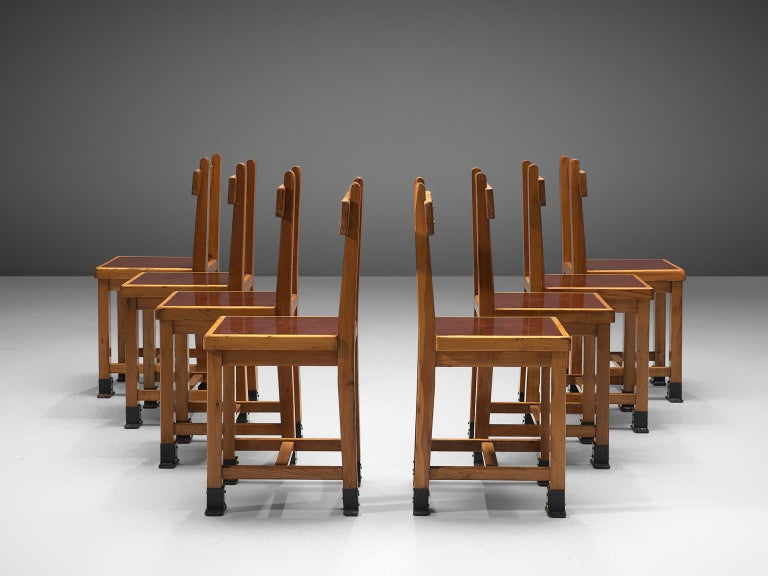 Set of eight dining chairs, oak, France, 1940s.  This set of unique and sturdy dining chairs has both a hint of Art Deco and minimalism at the same time. The patinated oak is simply wonderfully matched with the red lacquered seating. But what is