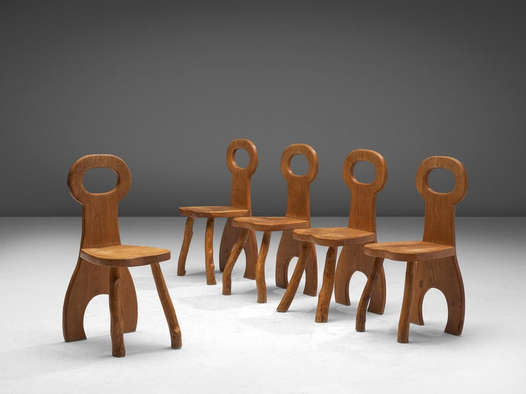 Set of five dining chairs, oak, France, 1960s.  Oak wooden chairs that has robust design with organic elements. The bulky seats are made of beautiful oak wood that developed a nice, rustic patina over the years. The design features a bulky and