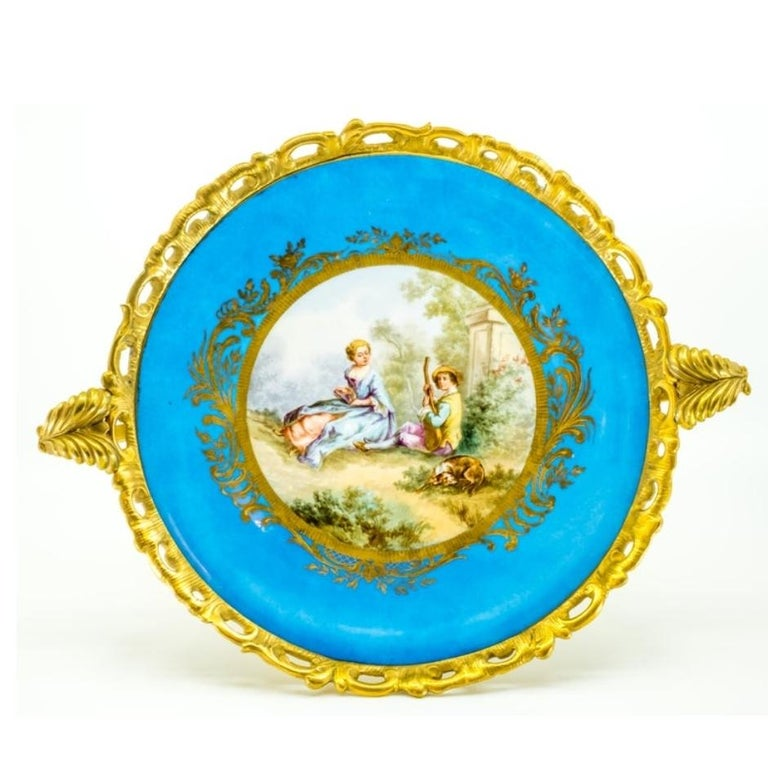 This French Sèvres-style porcelain plate from the 19th century is set in a gilt bronze mount, ormolu that features a Rococo base, rim and two handles with stylized foliage and C-scrolls. The center of the porcelain plate displays a pastoral scene