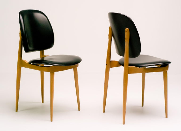 Pair of elegant chairs in maple and black vinyl. Priced individually.