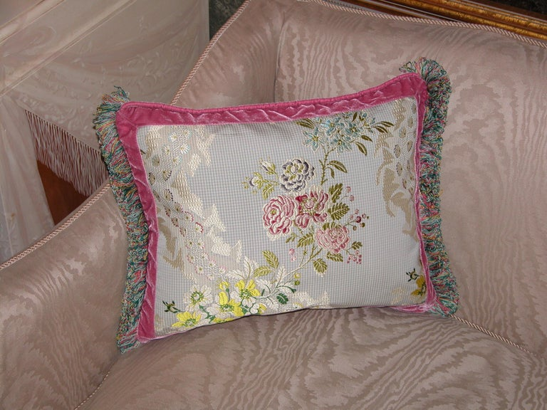 Throw pillow made from a French silk brocade woven in the 1990s, likely by Old World Weavers. Measures 13 inches x 17 inches. The trims include a silk velvet flat trim and a loop fringe by Passementerie, Inc.