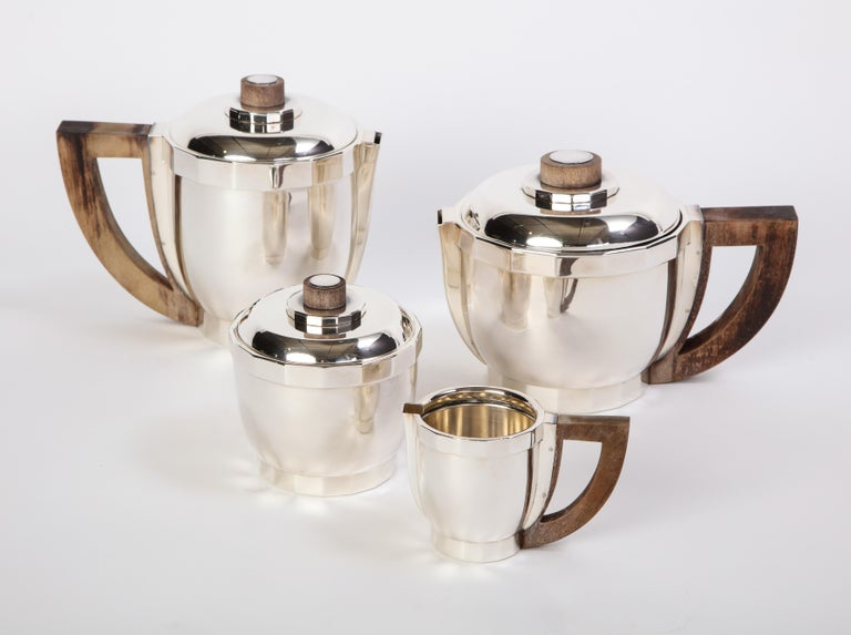 A French silver-plated Puiforcat four-piece tea and coffee service with wooden handles. Comprising a teapot, a coffee pot, a creamer, and a covered sugar bowl. All pieces are marked underfoot for Puiforcat France, circa 1990. The polished silver