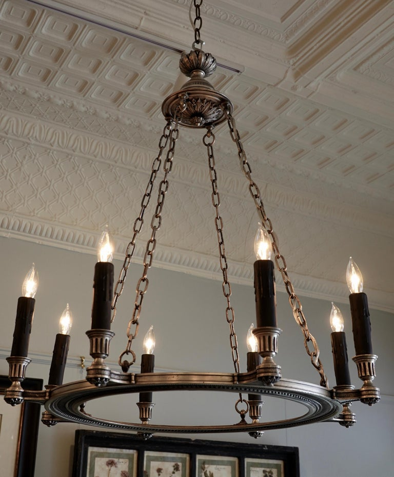 An elegant French silvered-bronze chandelier in the neoclassical style, suspended by four chains. The chandelier has be rewired with eight lights for the US. The frame features nicely chiseled details including rosettes, pearl beading and