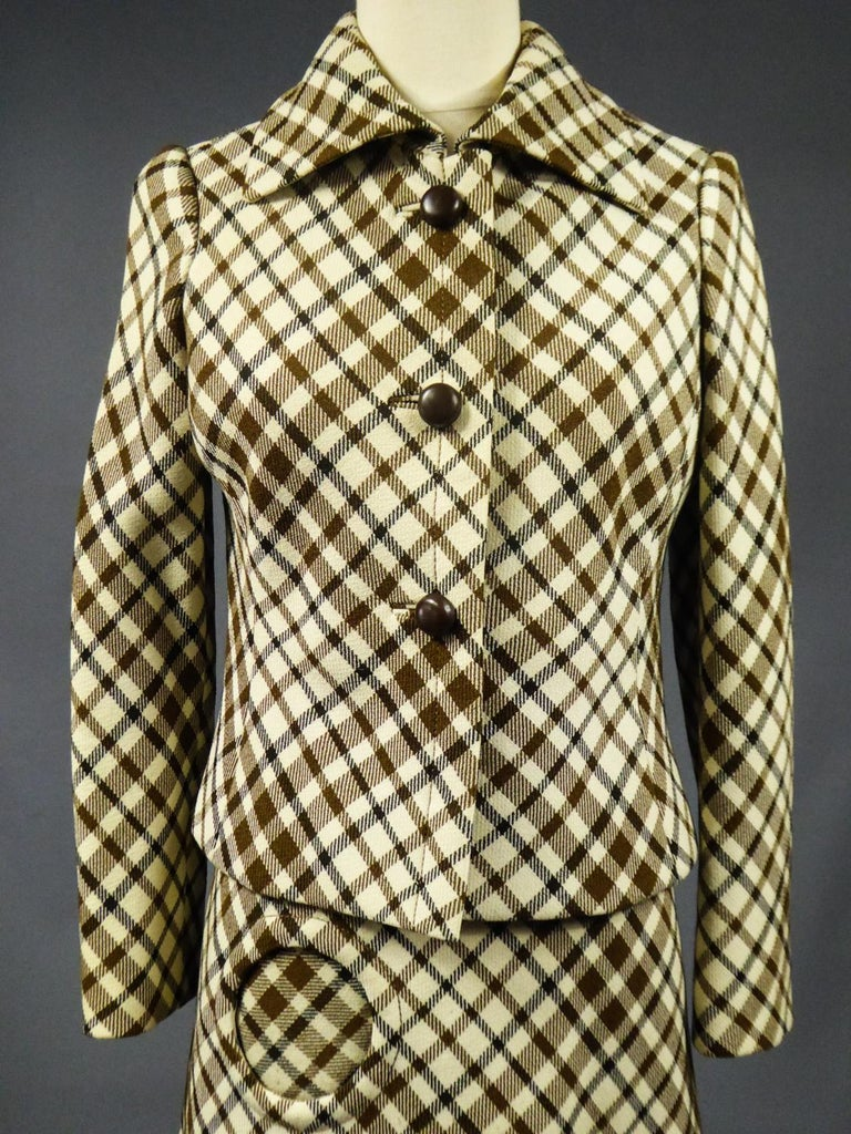 Circa 1968 France  Checked Skirt Suit inwool demi-Couture Christian Dior signed byBérénice Haute Couture in Marseille and dating from the Modernist period of the late 1960s. Fittedjacket with front closure by three buttons in brown plastic and