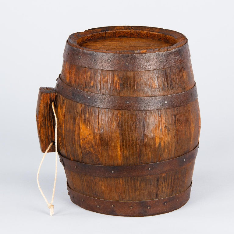 A handsome small oak Wine Barrel from Provence with nailed iron straps. A very decorative piece for the kitchen or the wine room. The rope was added later to hang barrel. The original cork is missing.