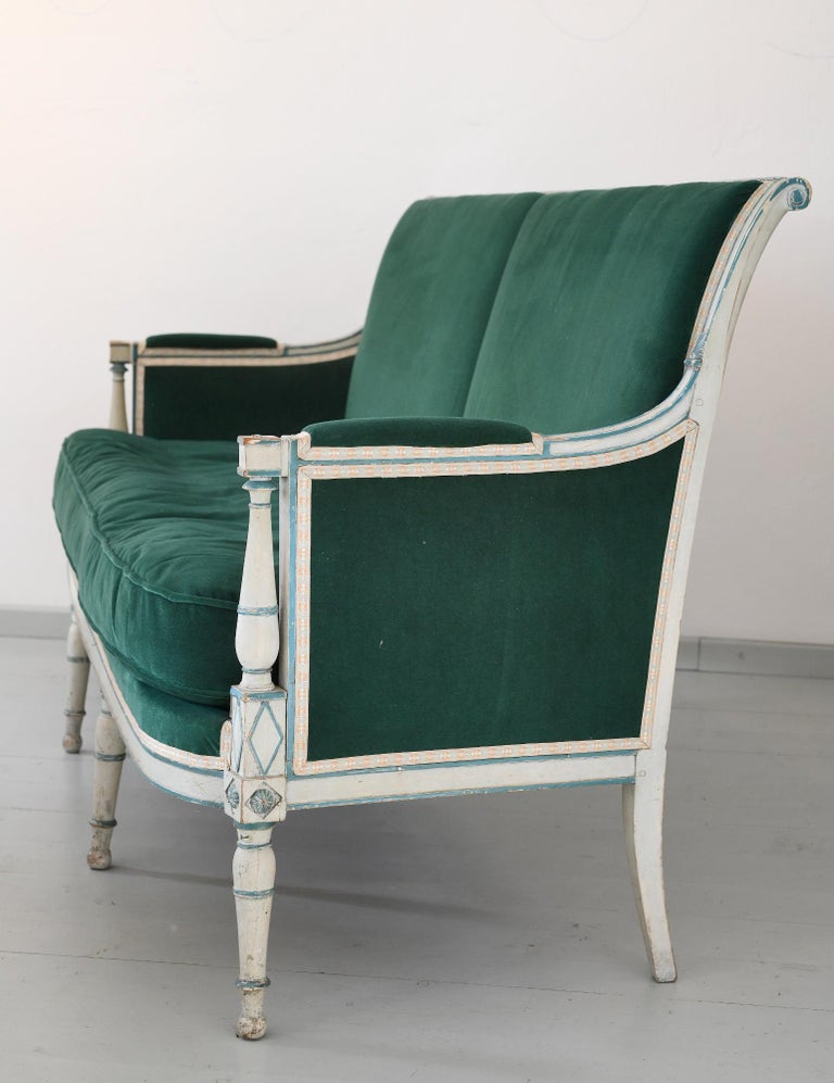 French sofa or canape directoire with elegantly moulded frame. It is grey and green painted and the original surface is wonderfully carved. The sofa is new upholstered with an comfortable mohair fabric and the pillows are filled out with downs. The