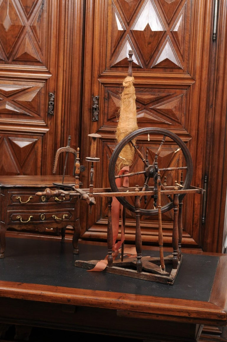 A French rustic spinning wheel from the 18th century, with original parts. Created in France during the 18th century, this spinning wheel will be an excellent decorative addition to any home. The wheel, connected to the treadle thanks to a turned