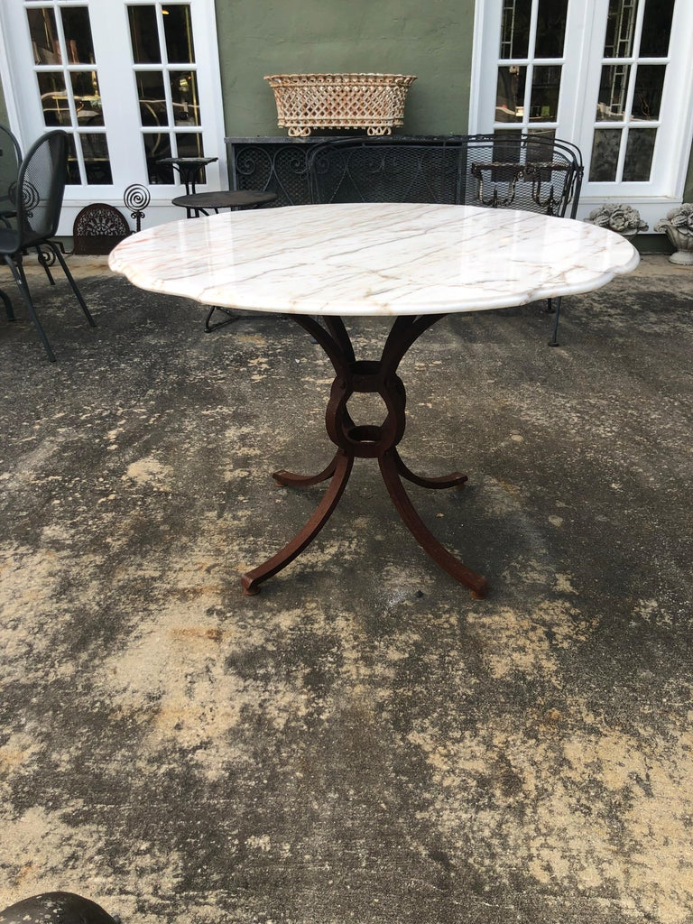 French style marble-top iron dining table. Heavy weathered Iron base most likely hand forged and one of a kind. Marble top is weathered too from being outside. Marble is stamped made in Belgium. The marble top has wooden underside base which screws