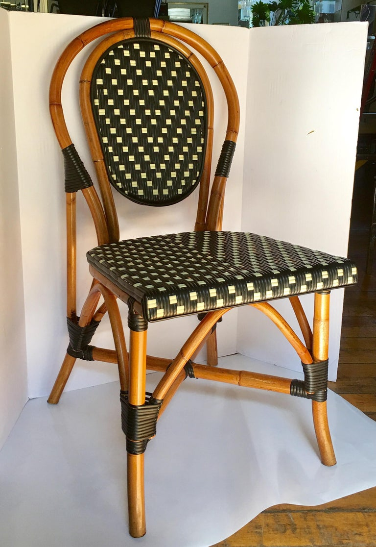 Classic French style bistro dining side chairs just like those you find in a Paris café. Frames expertly hand crafted of natural Malacca/Manau steamed bent cane with neutral black/ivory woven nylon seats and backs. For indoor and outdoor use under